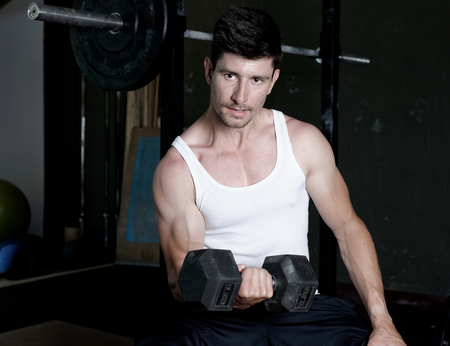 musculation: Fit men training his bicep at the gym