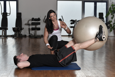 fitness training: Man exercising with his personal trainer at the gym. Stock Photo
