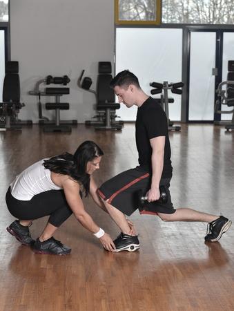 aide à la personne: Femme formateur de travailler avec elle stagiaire avec l'équipement de formation de poids