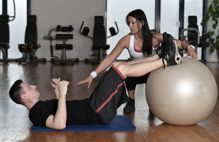 personal trainer woman: Man exercising with his personal trainer at the gym. Stock Photo