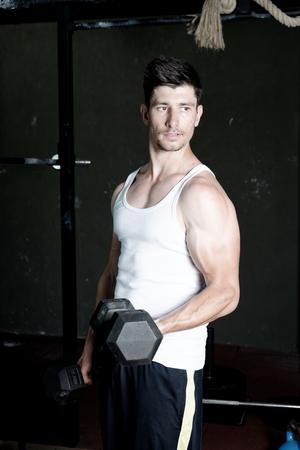 muskeltraining: Fitness Trainer Ausbildung seinen Bizeps in der Turnhalle