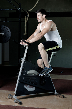 spin: Focused fit man on the spin bike at the gym