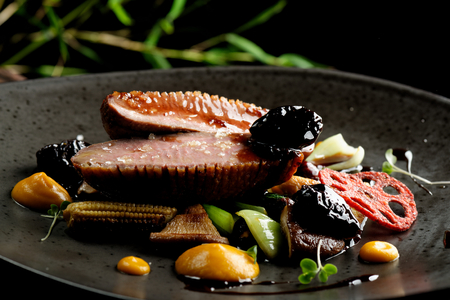 Haute cuisine/Asian fusion, roasted duck with plums and shiitake mushrooms Stock Photo