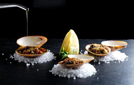 Haute Cousine, cozze vongole al forno gratinate sui cristalli di sale con olio d'oliva Archivio Fotografico - 45616244