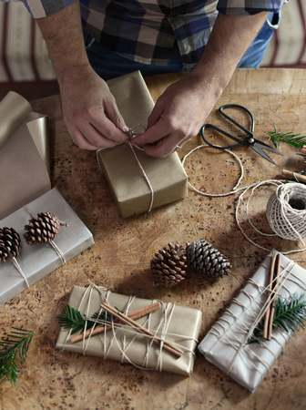 Young man wrapping his chic modern Christmas gifts presents on the wooden table