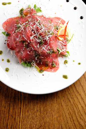 fine dining: Fine dining, Beef carpaccio with pesto genovese, parmesan cheese, capers and rocket salad
