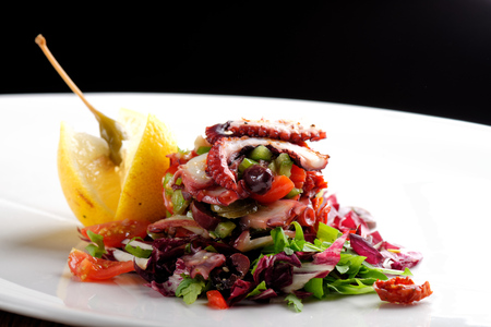 slice tomato: Fine dining octopus salad with lemon slice, tomato and lettuce Stock Photo