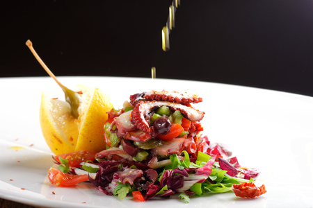 restaurant dining: Fine dining octopus salad with lemon slice, tomato and lettuce Stock Photo