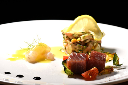 Fine dining seafood appetizer with Tuna Sashimi, octopus salad and shrimps