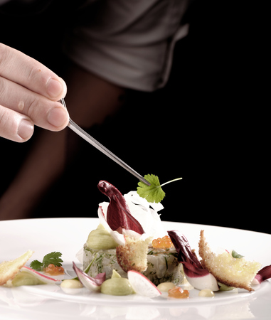 professional chef: Male chef garnishing his dish, ready to serve