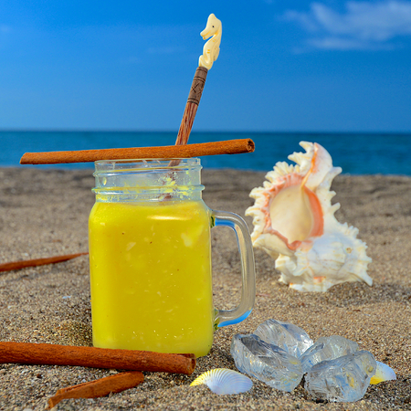 enjoyable: Colourful pineapple-cinnamon cocktail served on a golden beach at a tropical holiday resort during an enjoyable summer vacation