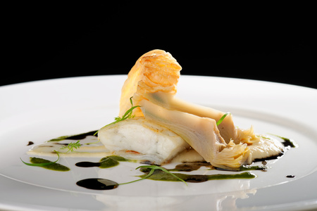Fine dining, baked cod fillet with spinach sauce and roasted onions