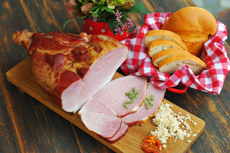 Delicious smoked ham on a wooden board with spices