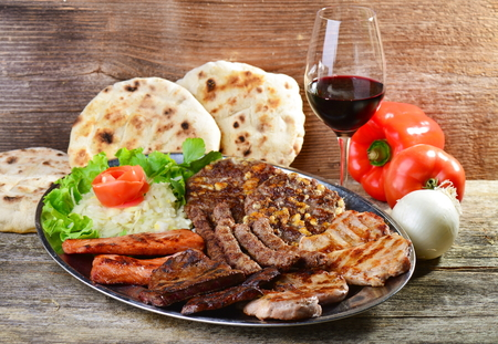 Wholesome platter of mixed meats including grilled steak. Balkan food Imagens