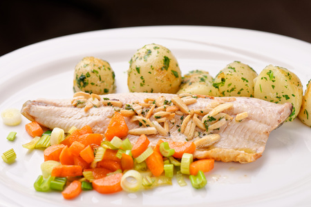 fine fish: Closeup of fine dine dinner Plate with Grilled White Fish and Vegetables Stock Photo