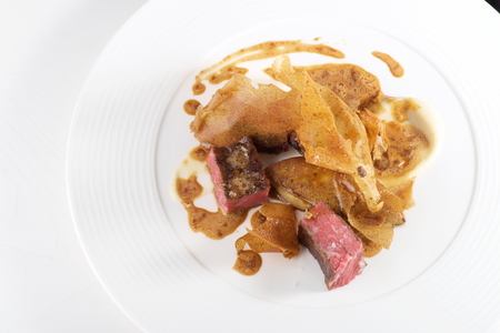 jerusalem artichoke: Fine dining, Beef ribs with Foie Gras and Jerusalem artichoke chips Stock Photo