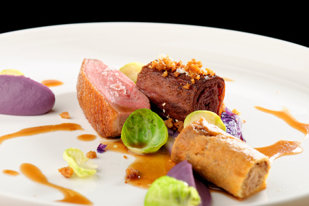 restaurant dining: Roast duck, red cabbage roll and dry fruits in fine dining restaurant Stock Photo