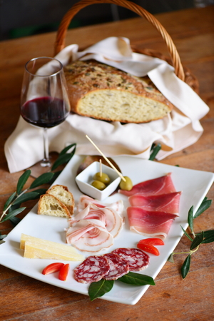 charcutería: Mediterranean charcuterie snacks, antipasto with bread, wine, salumi, nuts, olives and pickles