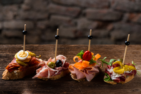 Tapas on Crusty Bread - Selection of Spanish tapas served on a sliced baguette. Stock fotó - 93284674