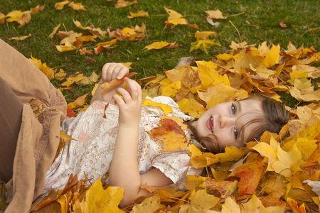 Jong meisje dat in bladeren het spelen ligt.