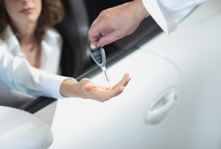 hand holding a car key and handing it over to another person.  photo