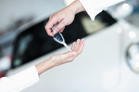 selling service: hand holding a car key and handing it over to another person.