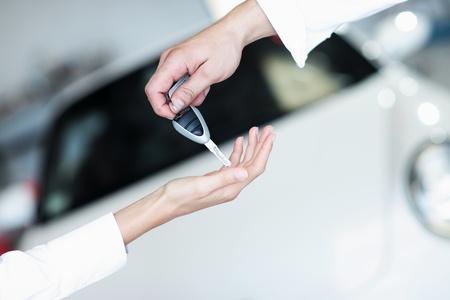 Mano che regge una chiave di auto e di consegnarlo ad un'altra persona. Archivio Fotografico - 10951587