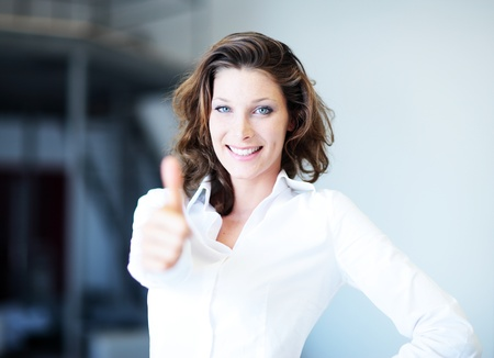 Confident business woman standing wearing elegant clothes with thumb up  photo