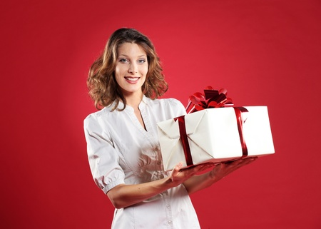 portrait of happy young woman with gift pack, red background photo