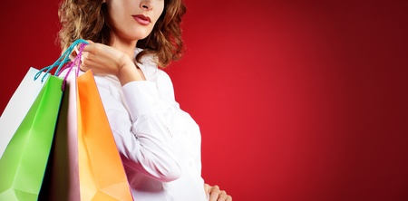 Woman holding shopping bags against a red background  photo