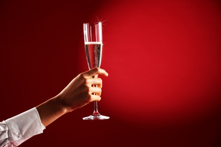 female hand with a glass of champagne on red background photo