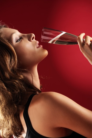 attractive young woman with a glass of champagne on red background photo