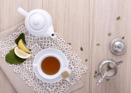 teapot with cup of tea, tea bag, lemon, sugar, photo