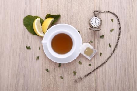 houten tafel met een kopje thee, horloge en citroen Stockfoto