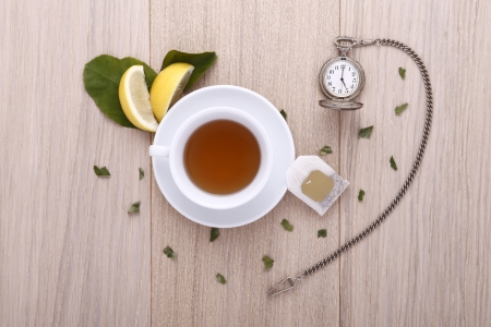 wooden table with cup of tea, watch and lemon photo