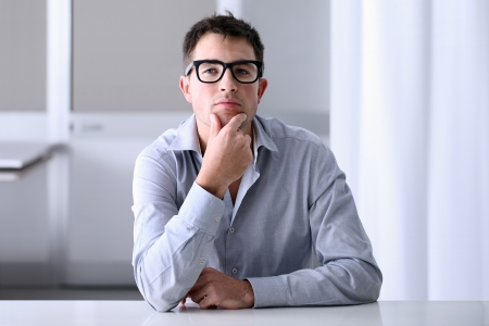 business concern: Man in home office with thoughtful look Stock Photo