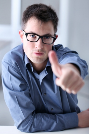 Man in home office showing his thumb, okay, sure, Stock Photo - 19177743