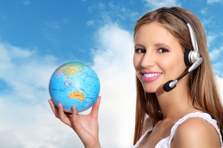 travel agency: receptionist with headphones and globe Stock Photo