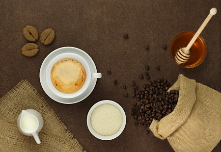 honey pot: cup of coffee on the table with beans, sugar, towel, bag, honey