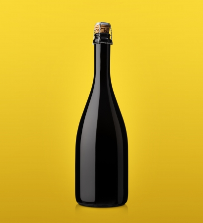 bottle of sparkling wine with cork on a colored background yellow photo