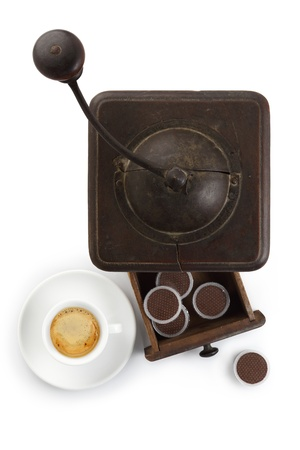 coffee grinder with cup of coffee and capsules