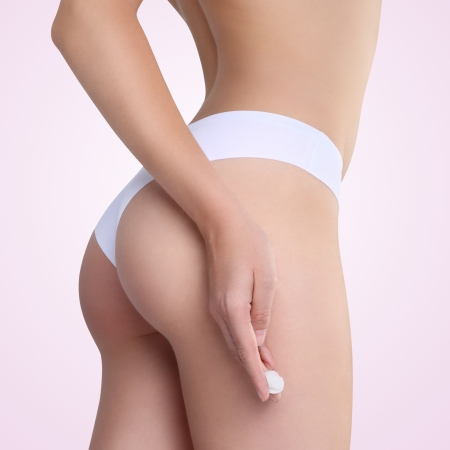 Female applying cosmetic cream from cellulite on the buttocks photo
