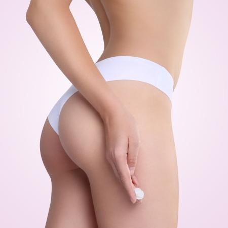 cellulite: Hembra que aplica la crema cosm�tica de celulitis en las nalgas Foto de archivo
