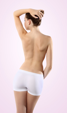 Body of woman ass and back on pink background photo