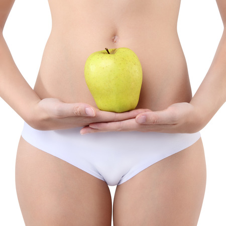 panties: woman holding an apple with his hands near the belly, over white background