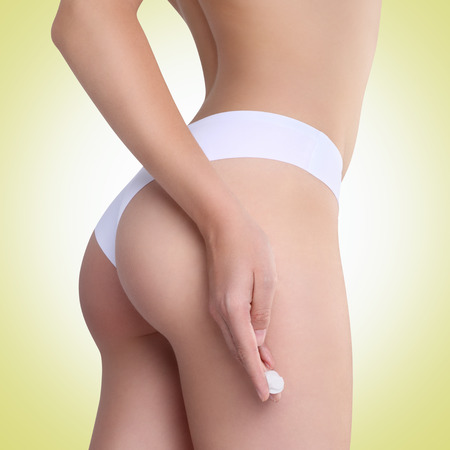 woman applying cosmetic cream from cellulite on the buttocks on a green background photo