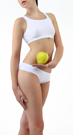 'flat stomach': woman holding an apple with his hands near the belly on white background