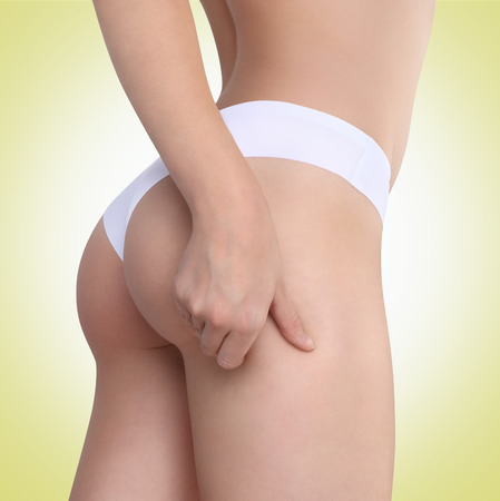Woman pinches her thigh to control cellulite on green background photo