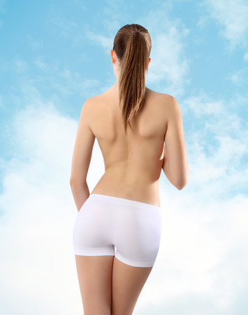 cintura perfecta: Cuerpo de mujer culo y la espalda en el fondo del cielo Foto de archivo