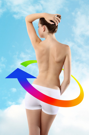 Body of woman ass and back on background of sky with colored arrow photo